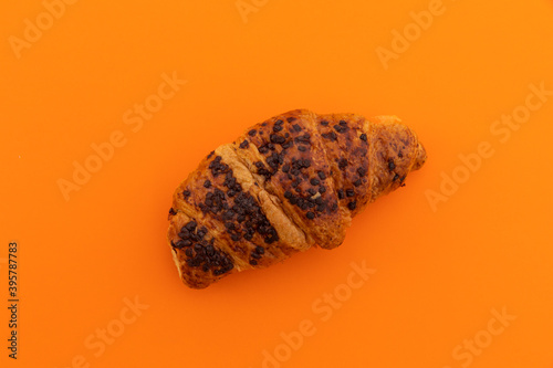 High angle view of chocolate croissant on orange background