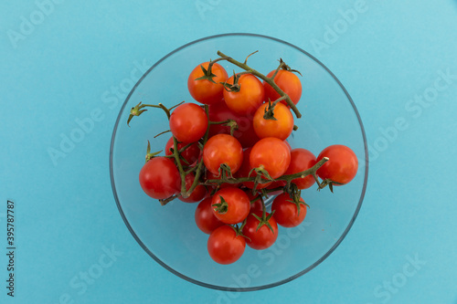 High angle view of bowl of fresh cherry tomatoes on blue background