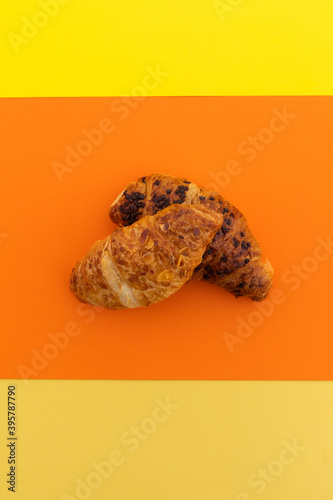High angle view of two croissants on orange background