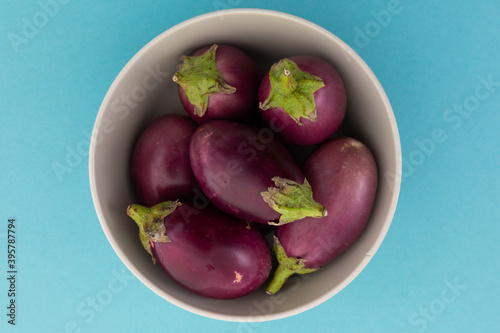 High angle view of bowl of fresh baby aubergine on blue background