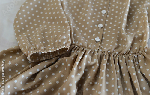 Fotomural A light beige dress with polka dots lies on the table