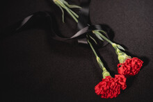 Top View Of Two Red Carnation Flowers With Ribbon On Black , Funeral Concept