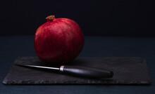 Ripe Red Pomegranates And Knife . Seasonal Fruits. Royal Fruit. Cutting A Pomegranate. On Black Background