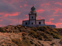 A View Of The Lighthouse At Akortiri In Santorini At Sunset In Summertime