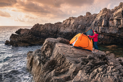 Female setting up tent foe camping on the rock above the sea Fotobehang