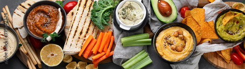 Different kinds of hummus dips with snacks Fotobehang