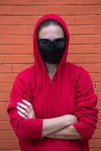 Woman Looks Straight In Camera. Red Sport Hoodie With Hood Put On Head In Black Sunglasses And Black Protective Medical Mask. Underground Style In Covid World. Orange Brick Wall Behind. Caucasian Girl