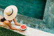 Young attractive woman in the pool enjoying delicious ripe watermelon. Bali Indonesia. Summer time, relaxation, travel content.