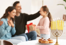 Menorah And Donuts On Table Of Happy Family Celebrating Hannukah At Home