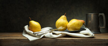 Three Pears On Old Wooden Table In Vintage Setting With Cutlery, Plate And Pewter Mug, Space For Text.