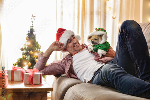 Fotomural Man resting on sofa with  dog dressed in christmas costume