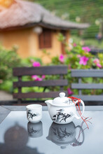 Teapot And Hot Tea To Cup On Wood Table Against Tea Garden View Background In The Morning, Ban Rak Thai Village, Mae Hong Son Province, Thailand