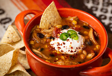 Bowl Of Chicken Taco Soup With Sour Cream And Tortilla Chips In An Orange Bowl