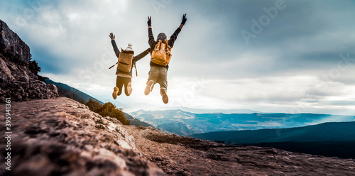 Obraz Successful hikers jumping on the top of the mountain - Happy couple with backpack enjoying life at sunset - fototapety do salonu