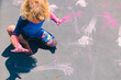 Blond child sitting on a grey trampoline leaving hand prints with a pink paint