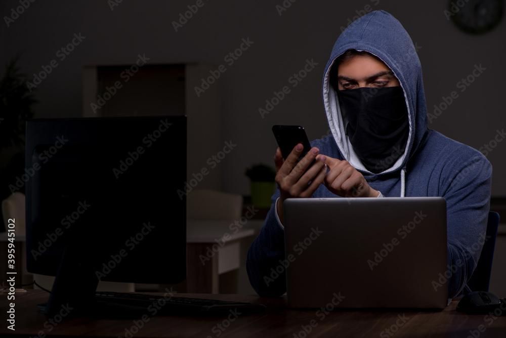 Fototapeta Male hacker hacking security firewall late in office