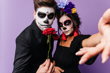 Lady With Crown Of Roses And Red Earrings Takes Selfie While Young Man With Face Art For Halloween Holds Rose