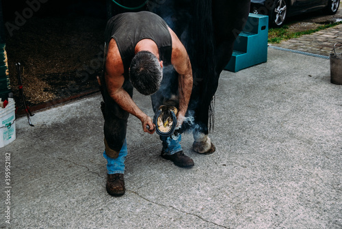 Closeup shot of blacksmith man putting a horseshoe on a horse Wallpaper Mural
