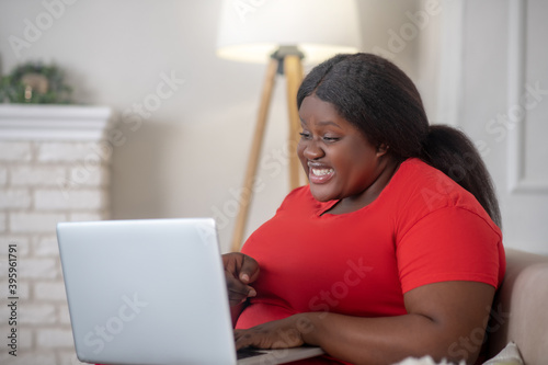 Foto African american woman sitting in her room with a laptop and looking surprised