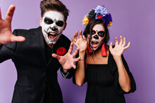 Closeup Portrait On Halloween Of Man And Woman Posing With Frightening Faces. Couple In Black Clothes With Red Details Screaming