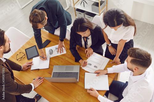 Sales team gather around office desk, analyze financial data and do paperwork using laptop computer