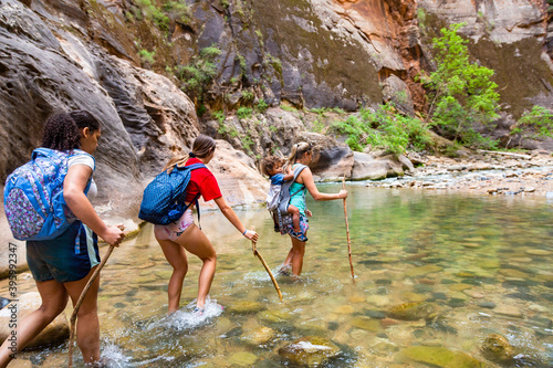 Fotografia Group of diverse people hiking through a river at Zion National Park