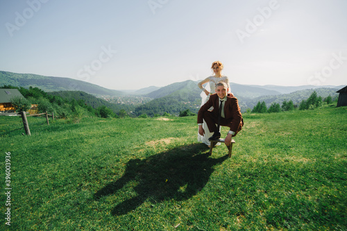 Fotografering happy stylish bride and groom running and having fun in mountains on summer sunny day