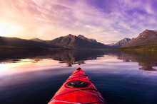 Kayaking In Lake McDonald With American Rocky Mountains In The Background. Colorful Sunset Sky Art Render. Taken In Glacier National Park, Montana, USA.