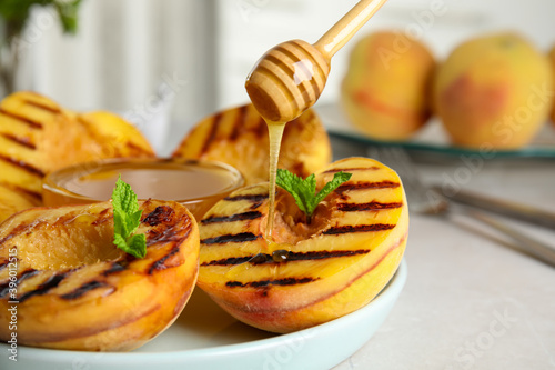 Fototapeta Pouring honey onto delicious grilled peaches on grey table, closeup obraz
