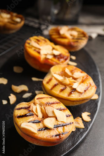 Fototapeta Delicious grilled peaches with almond flakes on grey table, closeup obraz