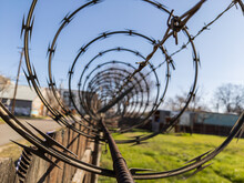 Closeup Of Barbed Wire On Top Of Fence