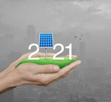 2021 White Text With Solar Cell On Green Grass Field In Man Hands Over Pollution City Tower And Skyscraper With Birds, Happy New Year 2021 Ecological Cover Concept