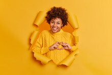 Lovely Smiling Woman Shapes Heart Gesture Being In Good Mood Expresses Love To You Says Be My Valentine Confesses In Truthful Feelings Wears Yellow Sweater Poses Through Paper Background In Hole