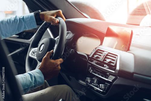 Fényképezés Male hands holding steering wheel of a car