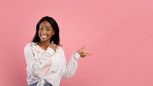 Smiling Black Woman Pointing Aside Over Pink Studio Background, Space For Your Advertisement Or Promo