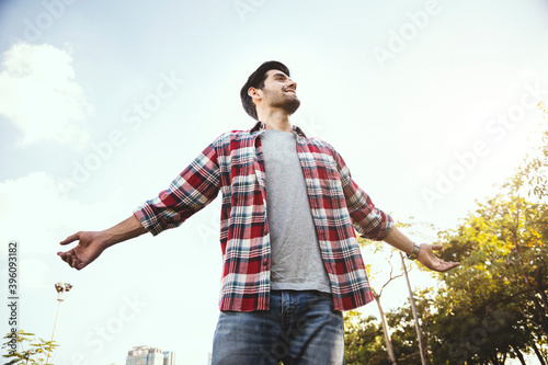 Carta da parati Caucasian man standing raised his hand in the park to breathe pure air, freedom, holiday