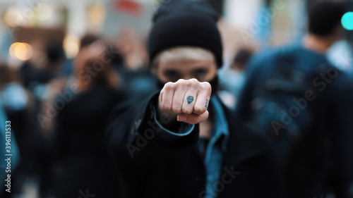 Fotografie, Obraz Portrait of fighting young angry rebellion women on the demonstrations punching air with the fist