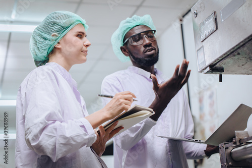Fotografie, Tablou Woman production supervisor working with African worker in food factory to checking and report machine problem to engineer in production line