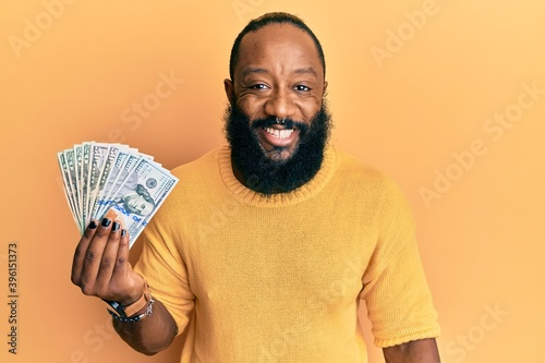 Fototapety, obrazy: Young african american man holding dollars looking positive and happy standing and smiling with a confident smile showing teeth