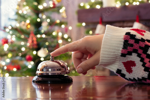 Hand of guest ringing reception bell on desk of guesthouse, hotel at christmas time Wallpaper Mural