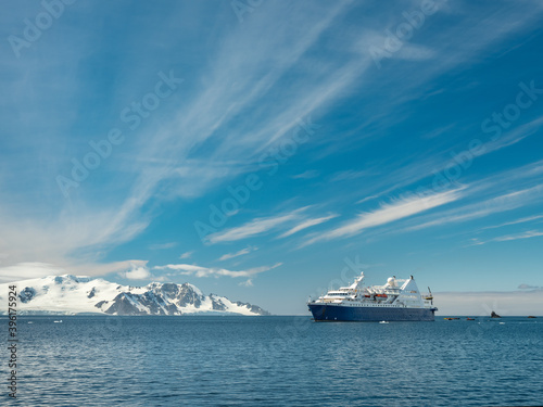 Tela view to passenger vessel in Antarctic waters under blue sky with light clouds an