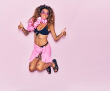 Young Beautiful Curly Woman With Tattoo On Vacation Wearing Bikini, Sunglasses And Hawaiian Lei Smiling Happy. Jumping With Smile On Face Doing Ok Sign With Thumbs Up Over Isolated Pink Background.