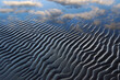 Blue sand ripples with clouds reflected in water