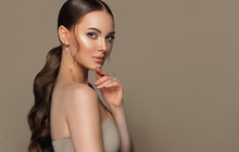 Beautiful Girl With  Curled Tail On Her  Head . Fashionable And Stylish Woman In Trendy Jewelry Big Earrings Rings  .  Fashion Look  , Beauty And Style. Natural Makeup & Easy Styling