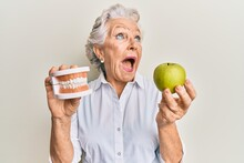Senior Grey-haired Woman Holding Green Apple And Denture Teeth Angry And Mad Screaming Frustrated And Furious, Shouting With Anger Looking Up.