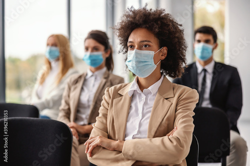 Papel de parede Young mixed race businesswoman sitting on seminar and listening presentation during corona virus outbreak