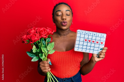 Fototapeta Young african american woman holding heart calendar and flowers looking at the camera blowing a kiss being lovely and sexy