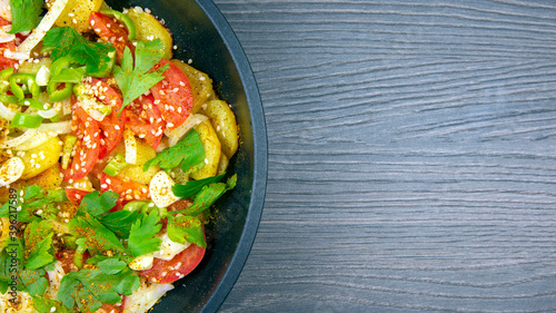 Fototapeta cooked fried potatoes with herbs, spices and vegetables in a black pan on a wooden table obraz