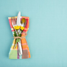 Summer Or Spring Table Setting With Teal Tablecloth, Silverware, And Multicolor Cloth Napkin With Yellow Daisy Flowers.  Background Has Copy Space.
