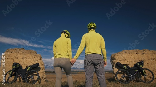The man and woman travel on mixed terrain cycle touring with bikepacking Fotobehang